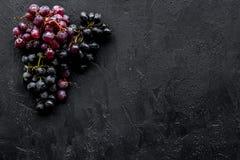 Ώριμο κόκκινο και μαύρο σταφύλι στη μαύρη τοπ άποψη υποβάθρου copyspace Στοκ φωτογραφίες με δικαίωμα ελεύθερης χρήσης
