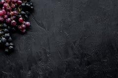 Ώριμο κόκκινο και μαύρο σταφύλι στη μαύρη τοπ άποψη υποβάθρου copyspace Στοκ Εικόνες
