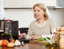 Ώριμο μαγείρεμα γυναικών με το σημειωματάριο Στοκ Φωτογραφίες