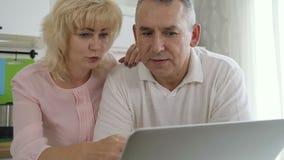 Ώριμο οικογενειακό ζεύγος που χρησιμοποιεί το φορητό προσωπικό υπολογιστή στην κουζίνα απόθεμα βίντεο