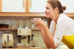 Ώριμο φλιτζάνι του καφέ κατανάλωσης γυναικών στην κουζίνα Στοκ Φωτογραφίες