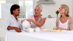 Ώριμο χύνοντας τσάι γυναικών στο φλυτζάνι φίλων της απόθεμα βίντεο
