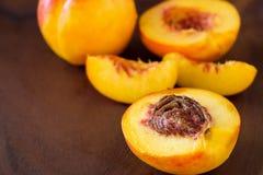 Ώριμο juicy σύνολο και φέτα φρούτων νεκταρινιών οργανικό στο ξύλινο β Στοκ Εικόνα