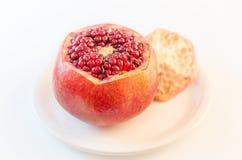 Ώριμο rpomegranate σε ένα άσπρο πιάτο στο πρώτο πλάνο που απομονώνεται στην άσπρη έξω--εστίαση υποβάθρου που θολώνεται Στοκ φωτογραφία με δικαίωμα ελεύθερης χρήσης