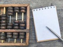 Абакус на деревянной предпосылке с космосом на белых тетради и ручке стоковые фотографии rf