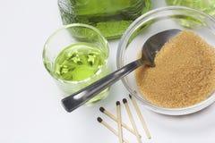 Абсент зелен В бутылке и политый в стекла Желтый сахарный песок для карамелизации питья и спички для горящего сахара стоковая фотография rf