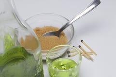 Абсент зелен В бутылке и политый в стекла Желтый сахарный песок для карамелизации питья и спички для горящего сахара стоковые изображения rf