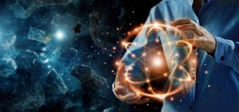 Абстрактная наука, руки держа атомную частицу, ядерную энергию стоковое изображение