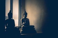 Абстрактная низкая ключевая светлая сторона изображения латунной статуи Будды Стоковое Изображение RF