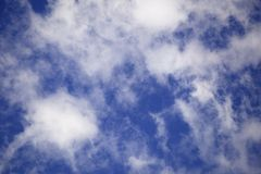 Абстрактная предпосылка белых просвечивающих облаков кумулюса на ярком голубом небе Стоковое Изображение