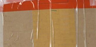 абстрактная предпосылка Часть коричневой упаковки перехода картона заштукатурила с покрашенными клейкая лента для герметизации тр Стоковая Фотография RF