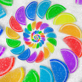 Абстрактная спиральная радуга студня плодоовощ заклинивает куски на предпосылке песка белого сахара Конфеты радуги jelliy Сладост Стоковые Изображения RF
