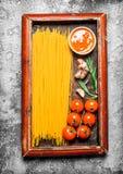 абстрактная текстура макаронных изделия еды предпосылки Спагетти с соусом и томатами в старом подносе Стоковая Фотография RF
