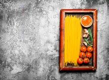 абстрактная текстура макаронных изделия еды предпосылки Спагетти с соусом и томатами в старом подносе Стоковые Фотографии RF