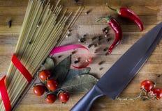 абстрактная текстура макаронных изделия еды предпосылки Сухие макаронные изделия с горячим перцем, томатами, луком, чесноком На ч Стоковое фото RF