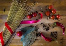 абстрактная текстура макаронных изделия еды предпосылки Сухие макаронные изделия с горячим перцем, томатами, луком, чесноком На ч Стоковое Изображение RF