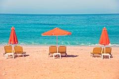 Абстрактное изображение с loungers солнца и оранжевыми зонтиками от s Стоковая Фотография RF