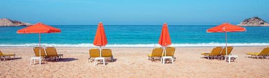 Абстрактное изображение с loungers солнца и оранжевыми зонтиками от s Стоковая Фотография