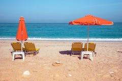 Абстрактное изображение с loungers солнца и оранжевыми зонтиками от s Стоковые Изображения