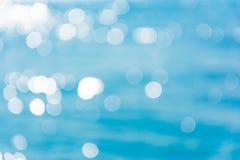 Абстрактное сияющее bokeh солнечного света на голубой предпосылке текстуры морской воды стоковое изображение rf
