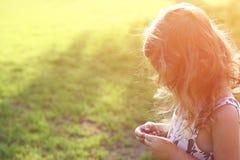 Абстрактное фото задней стороны счастливого ребенк играя на заходе солнца в парке, исследует и рискует концепцию стоковая фотография