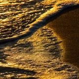Абстрактные формы ломая волн на песочном береге на заходе солнца Стоковое фото RF