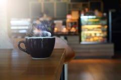 Абстрактный горячий черный кофе с деревянным столом стоковые изображения