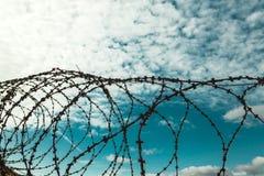 абстрактный колючий провод иллюстрации схематической конструкции Колючая проволока на предпосылке голубого неба с белыми облаками Стоковые Фото
