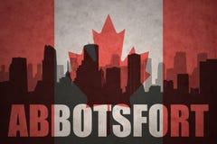 Абстрактный силуэт города с текстом Abbotsford на винтажном канадском флаге Стоковое Изображение