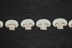 Абстрактный состав разделения вверх по коричневым грибам champignons помещенным в линии на каменной поверхности предпосылки стоковое фото