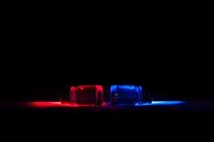 2 абстрактных зелья красного цвета и синего стекла под красочным светом Стоковая Фотография