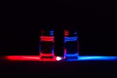 2 абстрактных зелья красного цвета и синего стекла под красочным светом Стоковое Изображение RF