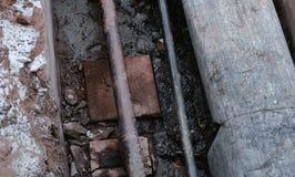 Авария крупного плана, трубы взрыва и протекая вода под землей Выкопенные экскаватором трубы в зиме Стоковые Изображения