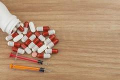 давать допинг спорту Злоупотребление анаболических стероидов для спорт Анаболические стероиды разлитые на деревянном столе Стоковое фото RF