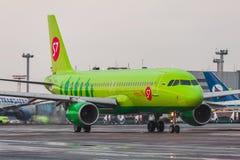 Авиакомпании аэробуса A320 S7 ездят на такси на авиапорте Domodedovo Москвы Стоковые Изображения RF