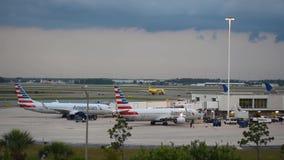Авиакомпании духа строгают скользить на взлетно-посадочной дорожке пока америкэн эрлайнз начинает двигать на международный аэропо