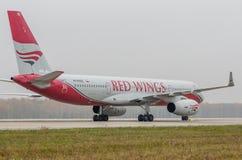 Авиапорт Domodedovo, Москва - 25-ое октября 2015: Туполев Tu-204-100B красного цвета подгоняет авиакомпаний Стоковое Изображение