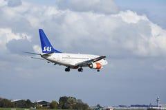 Авиапорт Schiphol Амстердама - Боинг 737 SAS (скандинавских авиакомпаний) приземляется Стоковое фото RF
