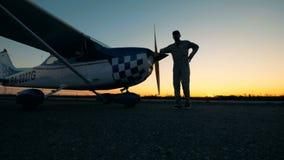 Авиатор идет к его самолету и полагается на ем видеоматериал