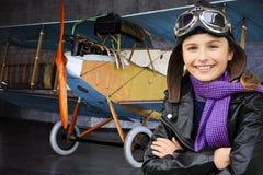 Авиатор, счастливая девушка готовая для того чтобы путешествовать с самолетом. стоковая фотография