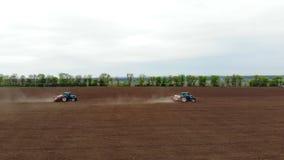 Авиационная съемка, весна, там 2 трактора в поле с особенными плантаторами точности, засаживают мозоль, или акции видеоматериалы