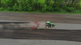 Авиационная съемка, взгляд сверху, весна, рыхлитель трактора культивирует, выкапывает почву r автоматизированный румпель сток-видео