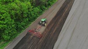 Авиационная съемка, взгляд сверху, весна, рыхлитель трактора культивирует, выкапывает почву r автоматизированный румпель видеоматериал