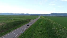 Авиационная съемка черный автомобиль двигая вдоль шоссе бесконечный горизонт сток-видео