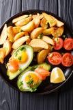Авокадо заполненный с яичками и семгами, свежими томатами и зажаренным p Стоковые Изображения