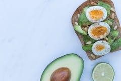 Авокадо и яичка на здравице коричневого хлеба Стоковые Изображения