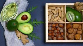 Авокадо, киви, грецкие орехи и миндалины, оливковое масло на доске сланца - еде богатой в хороших маслах Плоское положение стоковое изображение