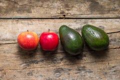 2 авокадоа и 2 яблока на деревянной предпосылке Стоковая Фотография