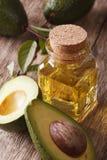 Авокадовое масло в конце-вверх стеклянной бутылки вертикально стоковые изображения rf