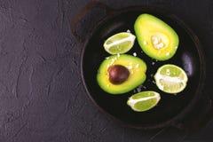 Авокадо, куски соли моря и известки на каменной предпосылке Стоковое Изображение RF